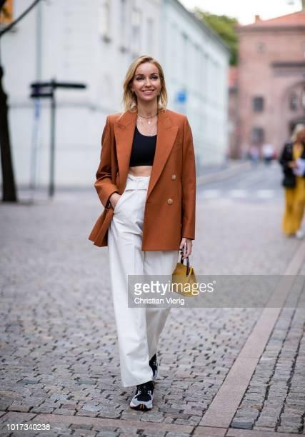 Hege Aurelie Badendyck wearing blazer white pants cropped top is seen outside FWSS during Oslo Runway SS19 on August 15 2018 in Oslo Norway
