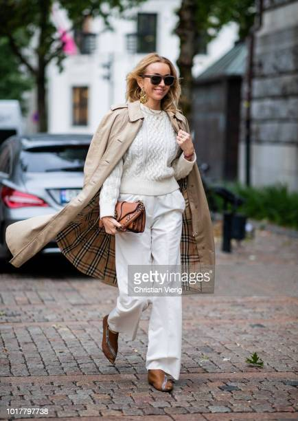Hege Aurelie Badendyck wearing white pants knit and beige trench coat is seen outside Bik Bok Runway Award during Oslo Runway SS19 on August 16 2018...
