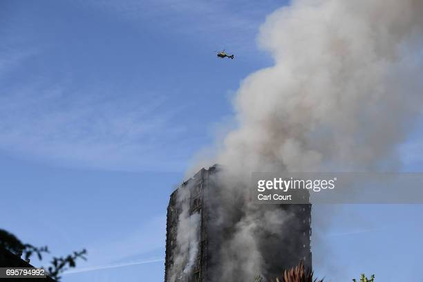 A heicopter circles as smoke rises from the building after a huge fire engulfed the 24 storey residential Grenfell Tower block in Latimer Road West...