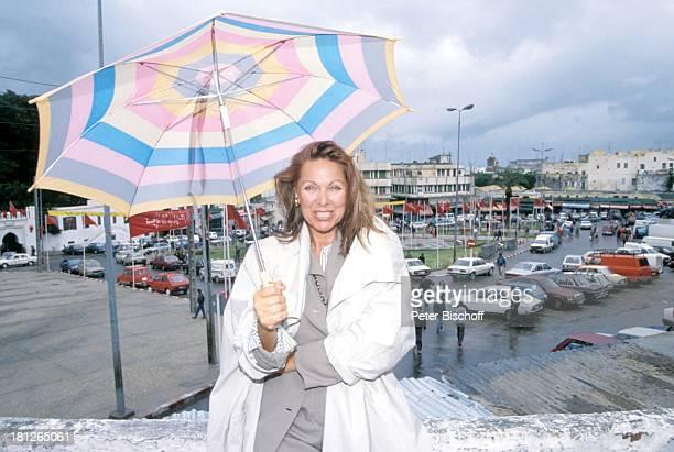 Heide Keller neben den Dreharbeiten zur ZDFReihe Traumschiff Folge 21 Ägypten MS Berlin Tanger/Marokko/Afrika Mantel Stadt Regenschirm Urlaub...