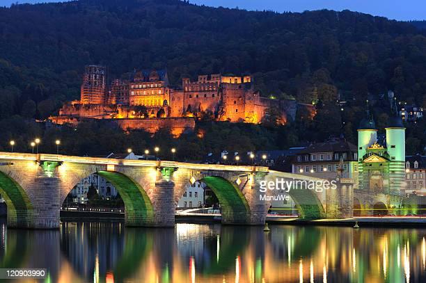 heidelberg illuminated palace bridge view evening summer - heidelberg stock photos and pictures