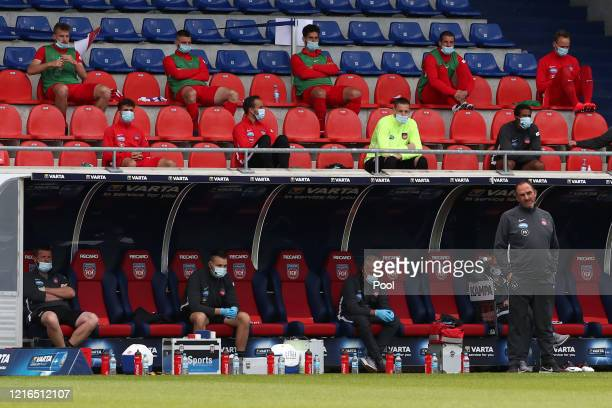 Heidenheim coach Frank Schmidt looks on as the substitutes are sitting in the stands above the bench during the Second Bundesliga match between 1 FC...