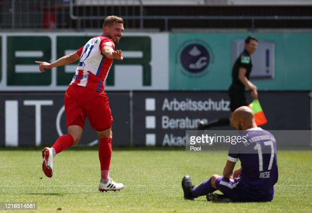 Heidenheim's Konstantin Kerschbaumer celebrates after he scores his teams second goal as Aue Philipp Riese sits on the pitch during the Second...