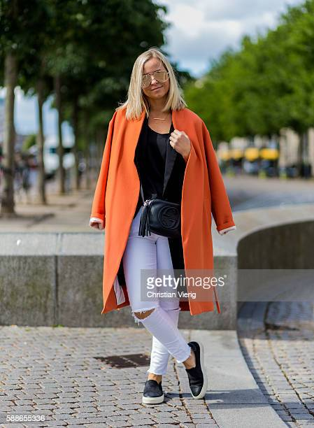 Heidi Aasheim Tragethon wearing an orange coat white ripped pants black Gucci bag and black slippers outside Revolver Fair during the second day of...