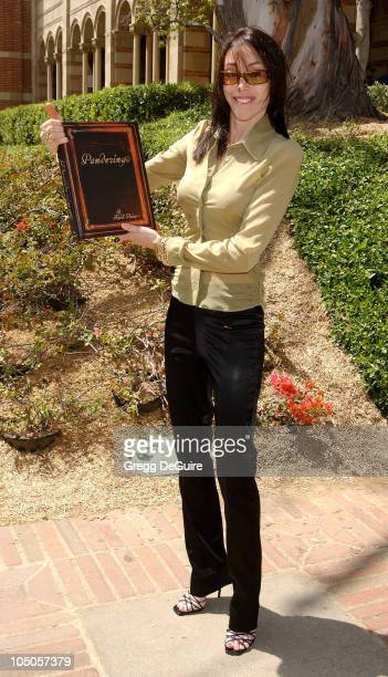 Heidi Fleiss posing with her new book Pandering