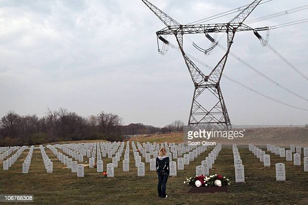 Heidi Franc stops to say a prayer at the grave of U.S. Army PFC Andrew Meari, of Plainfield, Illinois following a service at Abraham Lincoln National...