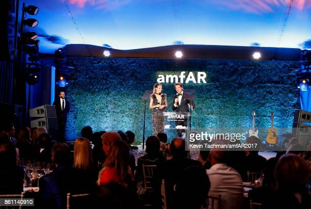 Heidi Klum and auctioneer Alexander Gilkes speak onstage at amfAR Los Angeles 2017 at Ron Burkle's Green Acres Estate on October 13 2017 in Beverly...