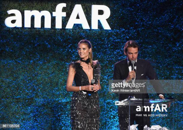 Heidi Klum and cofounder of Paddle8 Alexander Gilkes speak onstage at the amfAR Gala Los Angeles 2017 at Ron Burkle's Green Acres Estate on October...