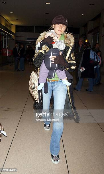 Heidi Klum carries her daughter Leni at JFK Airport in the early morning hours of January 17 2004 in New York City