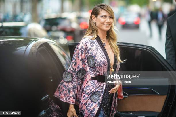 Heidi Klum wears earrings necklaces a lustrous beaded and embroidered floral print palepink kimonostyle long jacket a black velvet belt nacreous...