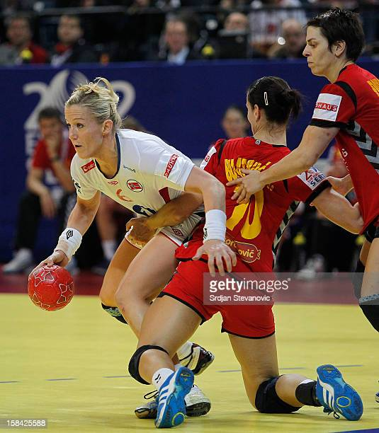 Heidi Loke of Norway is challenged by Andjela Bulatovic of Montenegro during the Women's European Handball Championship 2012 gold medal match between...