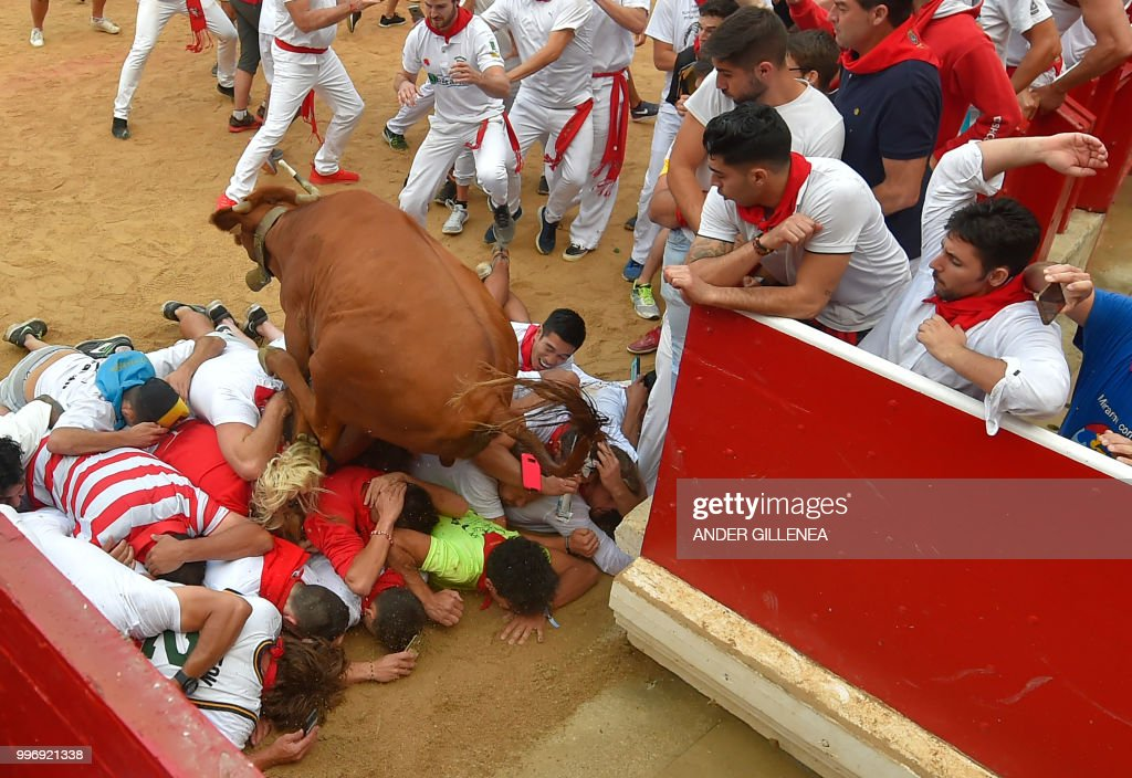TOPSHOT - A heifer jumps over revellers at the bullring during festivities of the San Fermin festival in Pamplona, northern Spain on July 12, 2018. - Each day at 8am hundreds of people race with six bulls, charging along a winding, 848.6-metre (more than half a mile) course through narrow streets to the city's bull ring, where the animals are killed in a bullfight or corrida, during this festival dating back to medieval times and also featuring religious processions, folk dancing, concerts and round-the-clock drinking.