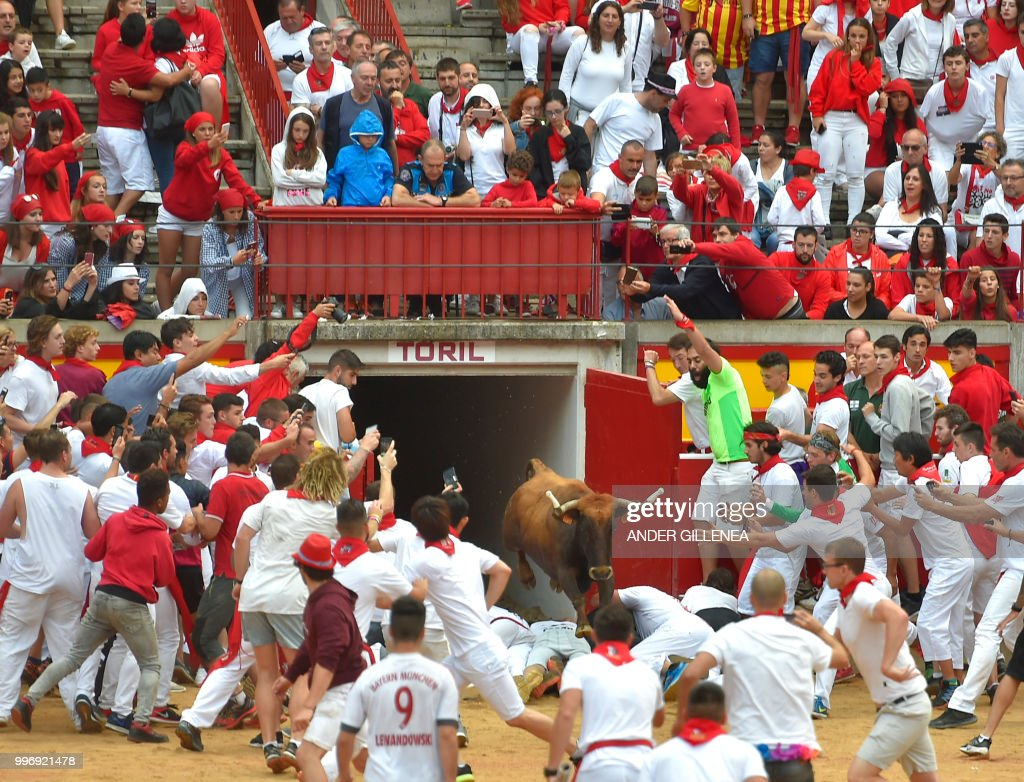 A heifer jumps over revellers at the bullring during festivities of the San Fermin festival in Pamplona, northern Spain on July 12, 2018. - Each day at 8am hundreds of people race with six bulls, charging along a winding, 848.6-metre (more than half a mile) course through narrow streets to the city's bull ring, where the animals are killed in a bullfight or corrida, during this festival dating back to medieval times and also featuring religious processions, folk dancing, concerts and round-the-clock drinking.