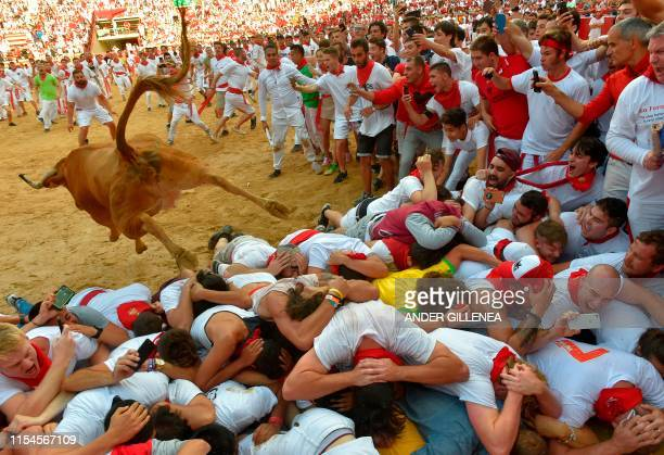 TOPSHOT A heifer jumps over revellers in the bullring after the second bullrun the San Fermin festival in Pamplona northern Spain on July 8 2019 On...