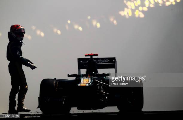 Heikki Kovalainen of Finland and Caterham stands beside his car after its engine blew up in the tunnel during practice for the Monaco Formula One...