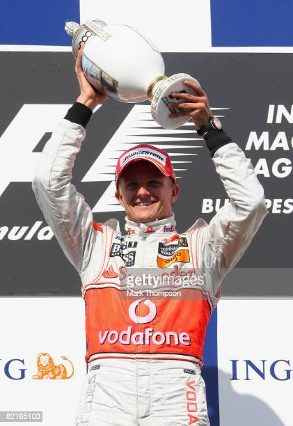 Heikki Kovalainen of Finland and McLaren Mercedes celebrates with the trophy on the podium following his victory at the end of the Hungarian Formula...