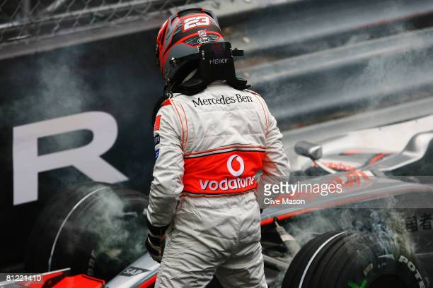 Heikki Kovalainen of Finland and McLaren Mercedes examines his car after spinning out while going through the swimming pool complex during the final...