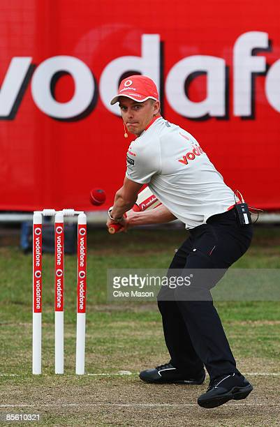 Heikki Kovalainen of Finland and McLaren Mercedes faces a delivery from Australian cricket legend Shane Warne in a 'backyard' cricket match in...