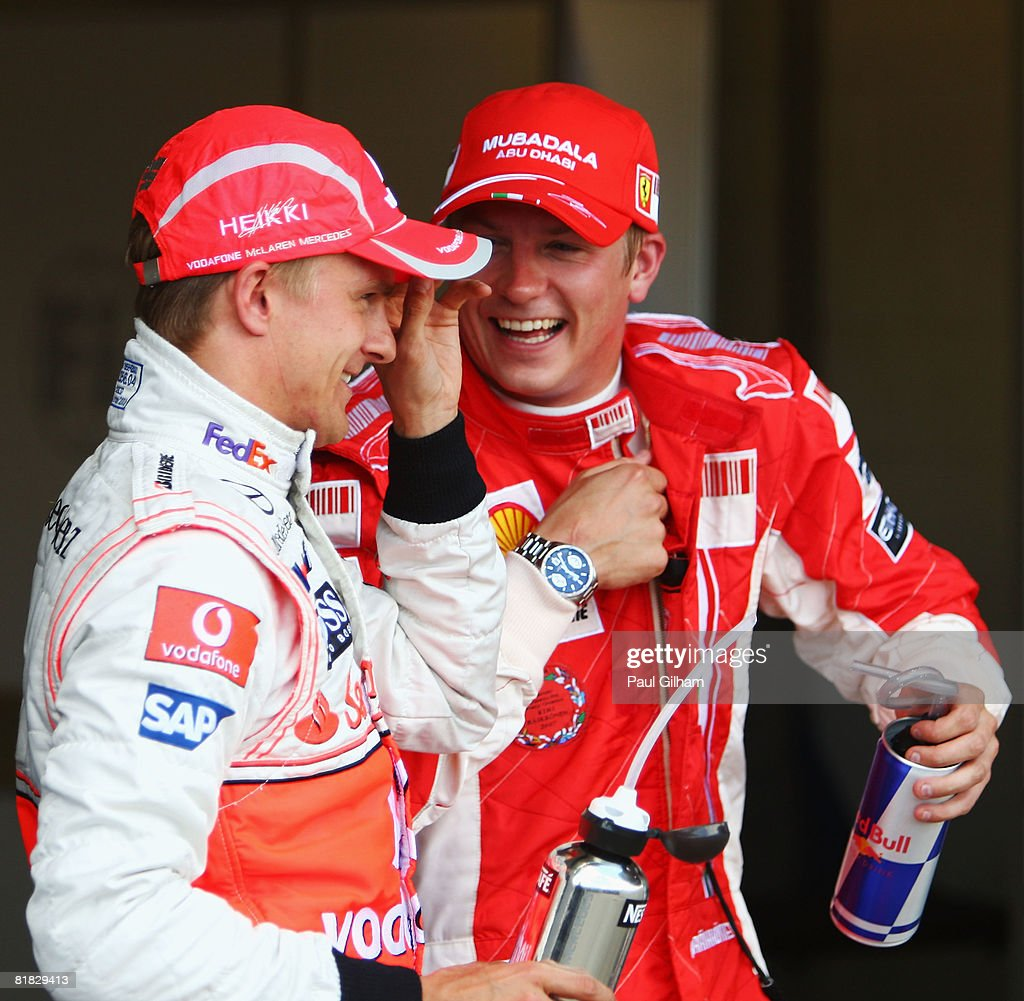 Heikki Kovalainen (L) of Finland and McLaren Mercedes talks with Kimi Raikkonen of Finland and Ferrari in parc ferme after taking pole position during qualifying for the British Formula One Grand Prix at Silverstone on July 5, 2008 in Northampton, England.
