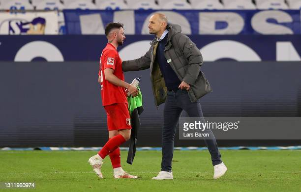 Heiko Herrlich, Head Coach of FC Augsburg interacts with Marco Richter of FC Augsburg after the Bundesliga match between FC Schalke 04 and FC...
