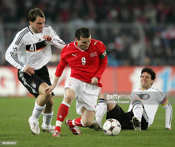 Heiko Westermann and Michael Ballack of Germany tackle Alexander Frei of Switzerland during the international friendly match between Switzerland and...