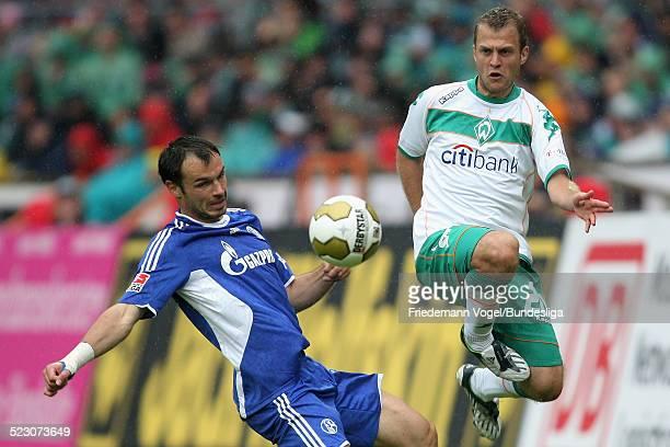 Heiko Westermann of Schalke challenges Daniel Jensen of Bremen for the ball during the Bundesliga match between Werder Bremen and FC Schalke 04 at...