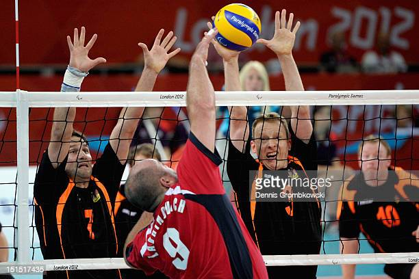 Heiko Wiesenthal of Germany and teammate Thomas Renger block a ball by Andrei Lavrinovich of Russian during the Men's Sitting Volleyball Bronze Medal...