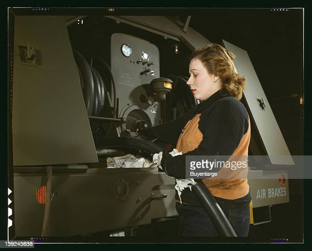 Heil and Co employee Agnes Cliemka checks the hoses of gasoline trailers before they are sent to the Air Force Milwaukee Wisconsin 1943