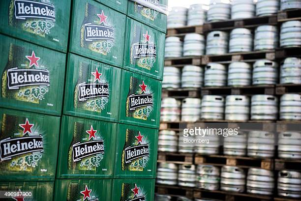Heineken branded crates stand stacked in front of pallets of beer barrels outside the Heineken Hungaria Breweries Plc Sopron brewery in Sopron...