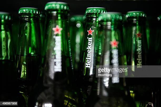 Heineken logos sit on the necks of beer bottles inside the Heineken Hungaria Breweries Plc Sopron brewery in Sopron Hungary on Thursday Nov 12 2015...