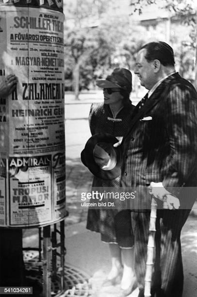 Heinrich George*09101893Schauspieler DBerliner Gastspiel in Budapestmit Ehefrau Berta Drews vor einer Litfaßsäule mit der Ankündigung der Aufführung...