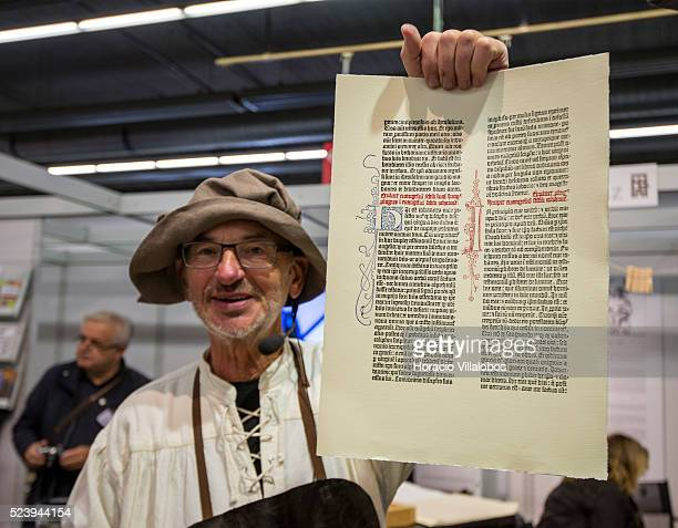 Heinz Noack shows a page printed with a replica of Gutenberg printing press at the Gutenberg Museum stand in 2013 Frankfurt Book Fair in Frankfurt...