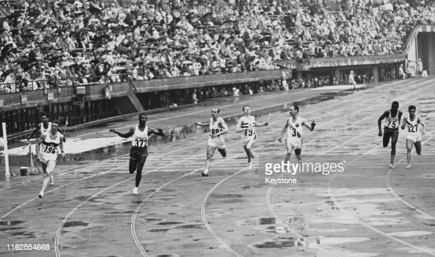 Heinz Schumann of the United Team of Germany leads Dennis Johnson of Jamaica and Bill Earle of Australia across the line to win heat 6 of the Men's...