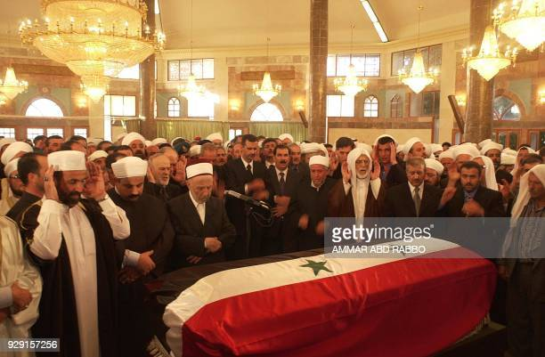 Heir apparent Bashar alAssad son of the late Syrian President Hafez alAssad prays surrounded by Muslim clerics over his father's coffin in Qerdaha 13...