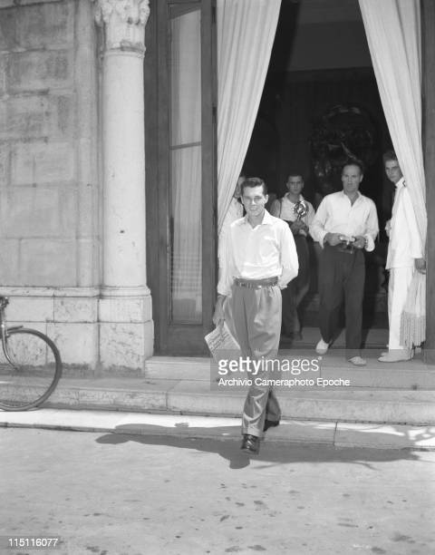 Heir Conrad 'Nicky' Hilton first husband of Elizabeth Taylor walking out of a building followed by photographers Venice 1950