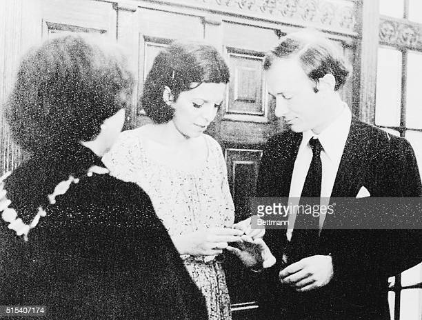 Heiress Christina Onassis places the wedding ring on the finger of Sergei Kauzov at wedding ceremony here August 1 His mother watches at left