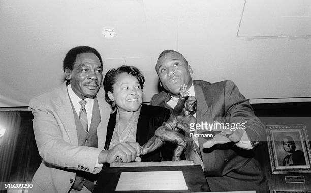Heisman Trophy winner Barry Sanders and his parents stand by the trophy he won as the outstanding college football player of 1988 during a ceremony...