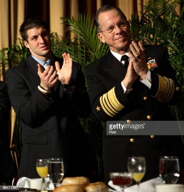 Heisman Trophy winner Tim Tebow and Chairman of the Joint Chiefs of Staff Michael Mullen applaud during the 58th National Prayer Breakfast on...