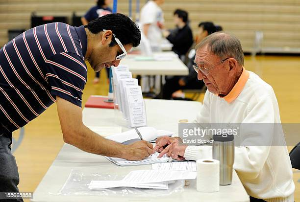 Hektor Esparza signs a voter log before he casts his ballot at the polling station at John Fremont Middle School on November 6 2012 in Las Vegas...