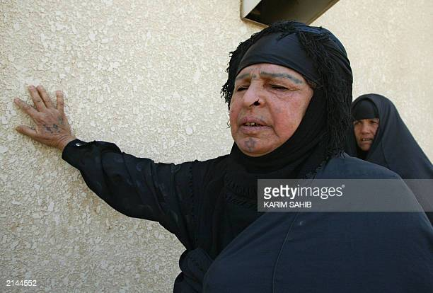 Hela the sister of Ibrahim Hamud holds herself up on the outside wall of the hospital after arriving to collect the decapitated body of her brother...