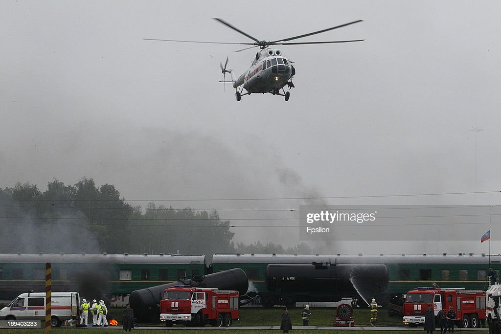 A helciopter flies above as Russian Emergency Situations Ministry douse a train during simulation exercises by the Russian Emergency Situations Ministry, at their Rescue Training Centre on May 24, 2013 in Noginsk, outside Moscow, Russia.