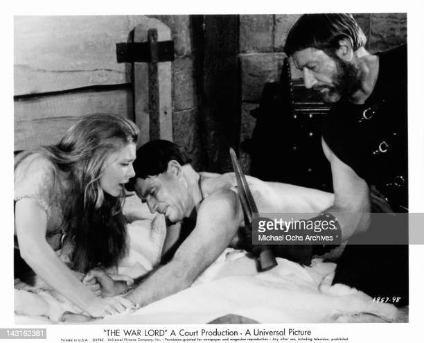 Held by Rosemary Forsyth Charlton Heston grimaces in pain as Richard Boone cauterizes his battle wound in a scene from the film 'The War Lord' 1965