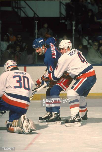 Held from behind by Canadian ice hockey player Paul Boutilier of the New York Islanders Ron Greschner of the New York Rangers tries to sneak the puck...