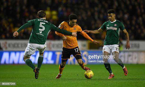 Helder Costa of Wolverhampton Wanderers gets past Andreas Bjelland and Ollie Watkins of Brentford during the Sky Bet Championship match between...