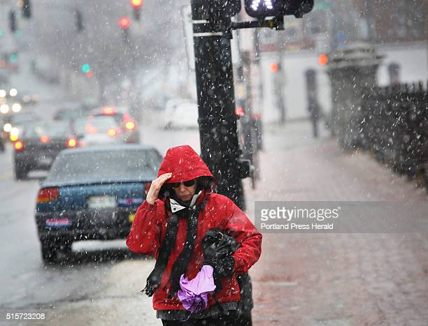 Helen Anderson of Portland holds the hood of her coat as she walks on Congress Street during a snow flurries on Monday March 7 2016