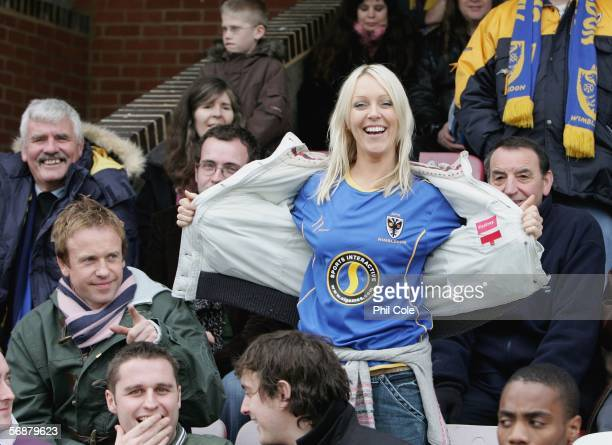Helen Chamberlain shows her Shirt while Tim Lovejoy on her right watches before the Ryman League Premier Division match between AFC Wimbledon and...
