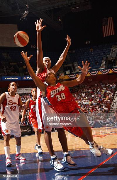 Helen Darling of the Charlotte Sting goes to the basket against Asjha Jones of the Connecticut Sun during the game at Mohegan Sun on August 18 2005...