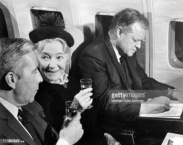 Helen Hayes and Whit Bissell holding wine glasses while Van Heflin looking at a map in a scene from the film 'Airport' 1970