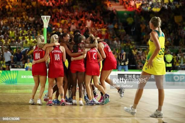 Helen Housby Geva Mentor and England celebrate winning as Australia captain Caitlin Bassett leaves the court during the Netball Gold Medal Match on...