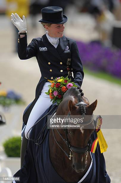 Helen Langehanenberg of Germany celebrates on her horse Damon Hill NRW after winning the Deutsche Bank Price freestyle dressage grand prix during day...
